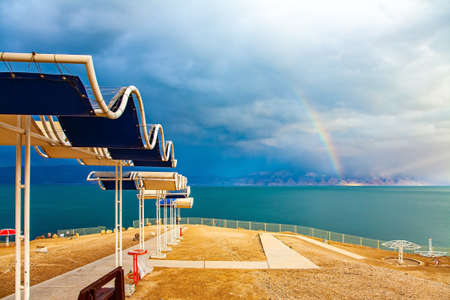 Picturesque beach with bright sunshades. The gloomy sky with dark thunderclouds and rainbow. The Dead Sea. Israeli coast. The exotic resort for treatment and relaxation Фото со стока