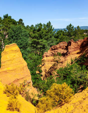 The rocks are covered with forest. The village of Roussillon. Provence, France. Brightly colored rocks lit by the midday sun. Walk along the most beautiful red-yellow-orange route.