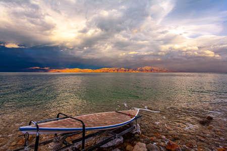 The Dead Sea, sunset. The sun illuminates the Jordanian coast. Gloomy sky with dark thunderclouds. Israeli coast. Rocky beach covered with evaporated salt.