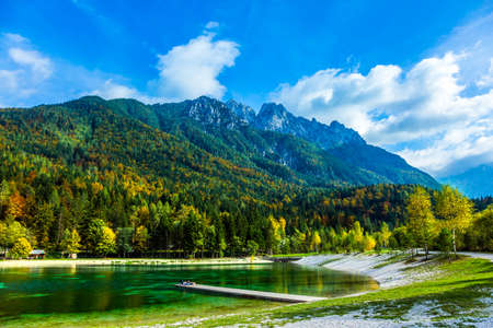 Lake Jasna in the Alps. The mountains are overgrown with dense mixed forest. Lake water reflects the sky. On the banks are lovely houses with red roofs