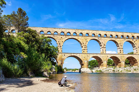 Photographer with a professional camera and a photo bag takes pictures of the famous aqueduct. The Gardon River. The Pont du Gard is the tallest Roman aqueduct. Interesting trip to France.
