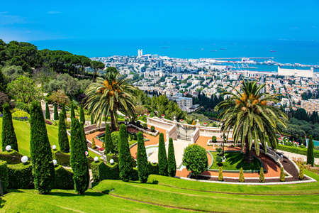 View from Mount Carmel to the international seaport of Haifa. Clear sunny day by the sea. Israel. Gorgeous colorful gardens, flower beds, cypress trees and green lawns attract tourists.