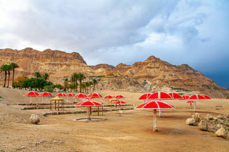Piicturesque beach with bright sunshades. The gloomy sky with dark thunderclouds and rainbow. The Dead Sea. Israeli coast. The exotic resort for treatment and relaxation. Фото со стока