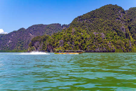 Boat ride to James Bond Island. Warm gentle Andaman sea and blue sky, picturesque cliffs overgrown with moss and grass. Travel to a fabulous warm country. Thailand