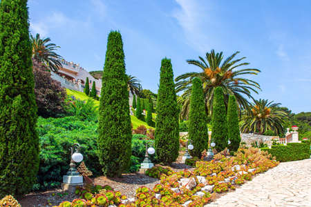 View from Mount Carmel to the international seaport of Haifa. Gorgeous colorful gardens, flower beds, cypress trees and green lawns attract pilgrims and tourists. Israel. Clear sunny day. Фото со стока
