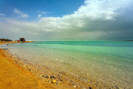 Beach after thunderstorm at the Dead Sea. Israel. The clouds are parting. Magnificent exotic resort for treatment and relaxation. The Dead Sea is a closed salt lake