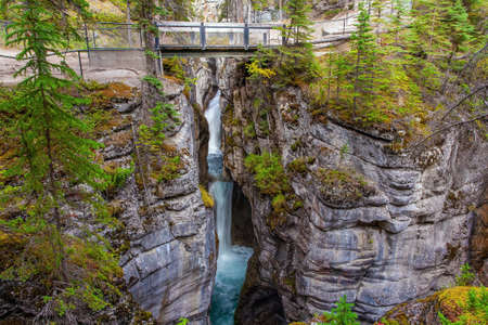 Tourist bridge over a magnificent cascading waterfall in a picturesque gorge Maligne Canyon. Cool cloudy day. Canada. Travel to the Rocky Mountains