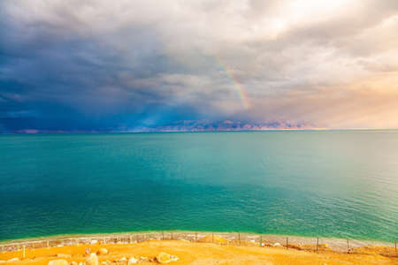 The Dead Sea is a closed salt lake. Israeli coast. Magnificent exotic resort for treatment and relaxation. Gloomy sky with dark thunderclouds merges with the surface of the water