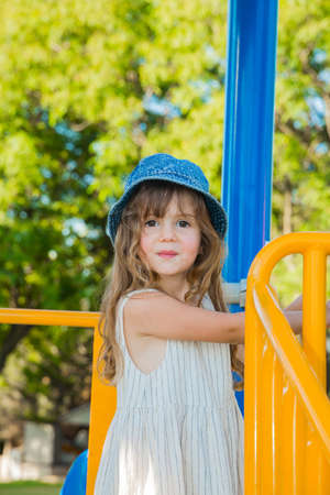 Warm summer day. Adorable little girl with long blonde hair in a white sundress and denim panama.  Attraction on the playground in green park