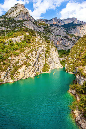French Alps. The azure waters of the Verdon mountain river splash beautifully in the gorge. Travel in pristine wilderness. The steep walls of the gorge are overgrown with bushes Фото со стока
