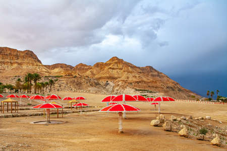 The gloomy sky with dark thunderclouds and rainbow. The Dead Sea. Israeli coast. The exotic resort for treatment and relaxation. Piicturesque beach with bright sunshades Фото со стока