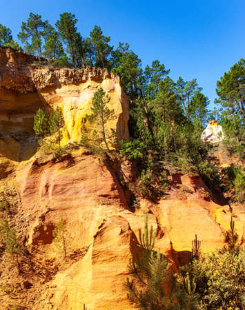 Bizarre ocher rocks. France, Provence. Walk along the most beautiful red-yellow-orange route. The rocks are covered with dense forest. The village of Roussillon. Sunny and warm day