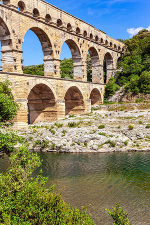 Masterpiece of ancient Roman architecture on the shallow Gardon River. The Pont du Gard is the tallest Roman aqueduct. The aqueduct is a three-tiered arcade of yellow-pinkish limestone. Фото со стока