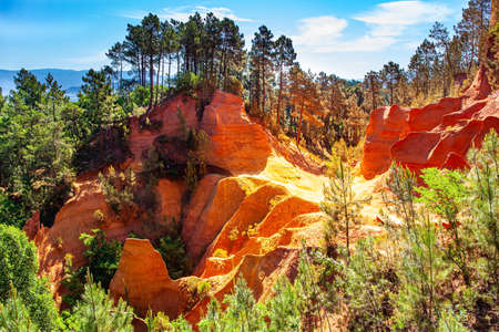 France, Provence. The village of Roussillon is surrounded by picturesque ocher cliffs. Now the rocks have grown into dense forests. Bizarre ocher rocks