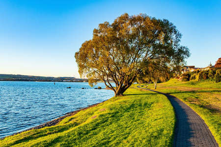 Nice walk by the lake. Magnificent sunset. Quiet evening on the lake. Taupo is the largest lake in New Zealand, North Island. The most popular holiday destinations for tourists.