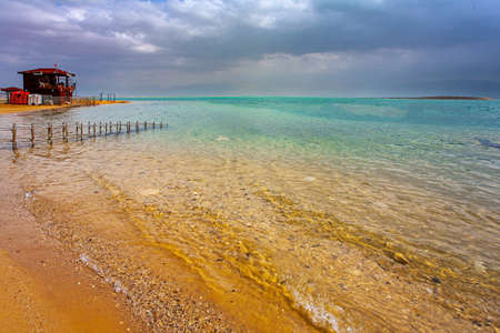 Dead Sea. Israel.  Gloomy sky with dark thunderclouds. Magnificent exotic resort for treatment and relaxation. Convenient gangway for descending into the water.