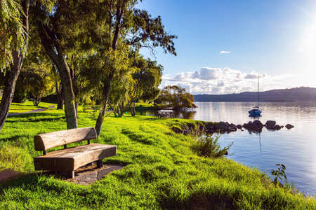 Comfortable wooden bench. The largest Lake Taupo in New Zealand. The magnificent lake is a popular holiday destination for tourists. Warm evening on the lake. Magnificent sunset. Фото со стока