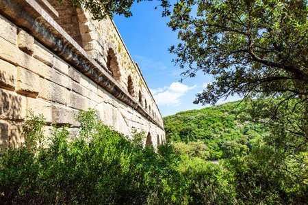 The aqueduct Pont du Gard connects mountains and hills covered with dense deciduous forest. The Pont du Gard is the tallest Roman aqueduct. Interesting trip to France. The shallow Gardon River