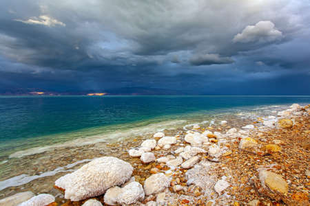 Rocky beach covered with evaporated salt. The Dead Sea is a closed salt lake. Gloomy sky with dark thunderclouds. Exotic resort for treatment and relaxation. Israeli coast.