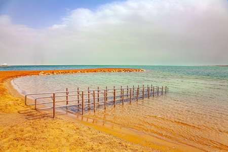 Convenient gangway for descending into the water. Dead Sea. Israel. Magnificent exotic resort for treatment and relaxation. Gloomy sky with clouds. Фото со стока