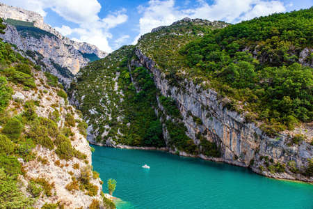 Beautiful French Alps. Tourist boats and catamarans float along the river. The steep walls of the gorge are overgrown with bushes. The most picturesque canyon in Europe - Verdon.