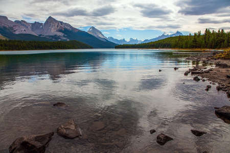Maligne Lake in Jasper, located in the Canadian Rockies in the province of Alberta. The lake is surrounded by mountain peaks and is very picturesque. Canada. Cloudy day Фото со стока