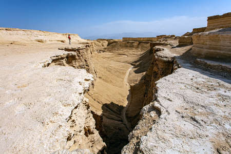 Woman tourist in a red sweater admires the landscape. The Judean Desert. Israel. Interesting walk among picturesque hills, cliffs and limestone gorges. Dead Sea.