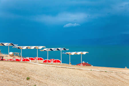 The Dead Sea is a closed salt lake. Israeli coast. Picturesque beach with bright sunshades. A gloomy sky with dark thunderclouds merges with the surface of the water.