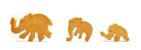 decreasing in size: Elefanti giocattolo in legno in una riga Archivio Fotografico