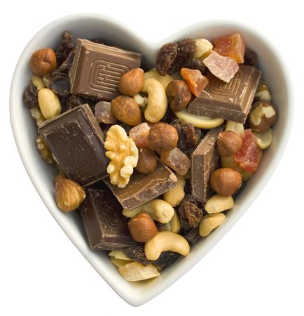 Heart shaped bowl filled with nuts, dried fruit and chocolate photo