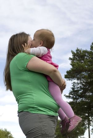 obese child: Sweet little toddler girl kissing obese mother.