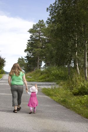 Obese mother and child walking on a forest path on a beutiful summer day. Stock Photo - 6965380