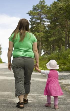 donne obese: Obese madre e figlio di camminare su una strada forestale in una bella giornata estiva.