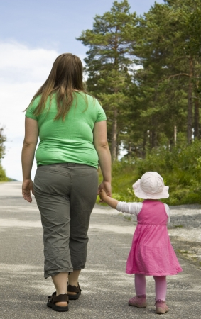 over weight: Obese mother and child walking on a forest path on a beautiful summer day.