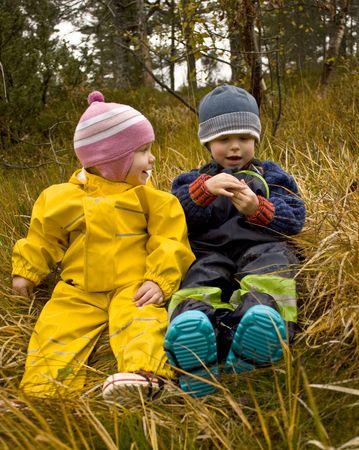 two people talking: Ni�os hablando juntos en un bosque de oto�o
