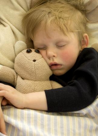 napping: Cute sleeping child cuddling his teddy bear