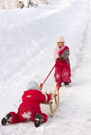 Children cooperating in getting a sleigh up a long hill.  Stock Photo - 7214323