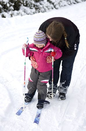 women children: Mother teaching small child cross country skiing