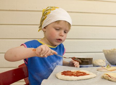 Small girl (3 years old) making a pizza.  photo