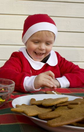 Child (3 years old) decorating gingerbread cookies with icing and chocolates. photo
