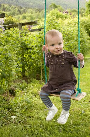 Sweet little blue eyed toddler on swing in a green garden photo