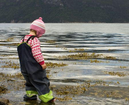 rainwear: Child (3 years old) wading into the sea.