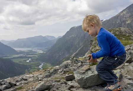 cairn: Small boy (3 years old) building a cairn on top of Litjfjellet. �ndalsnes in the background. Rauma, Norway.