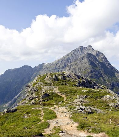 Narrow mountain path going up to a tall peak. Rauma, Norway Stock Photo - 7450976