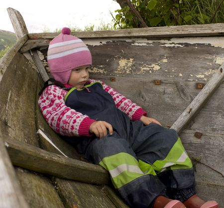 Bored and upset child (3 years old) sitting in an old boat. photo