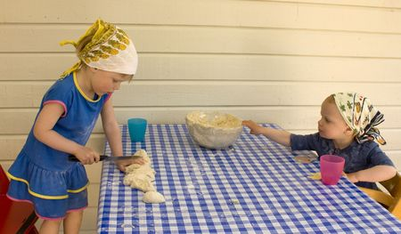 Small child (3 years old) cutting dough with a sharp knife,  toddler grabbing a heavy glass bowl.  photo