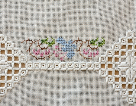 hardanger: Embroidered cloth on wooden table. With two different types of embroidery.