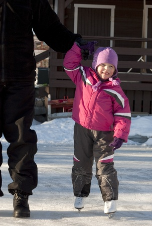 Adorable preschooler (4 years old) iceskating for the first time, holding her fathers hand photo