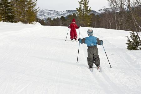 Happy small children meeting in the ski tracks photo