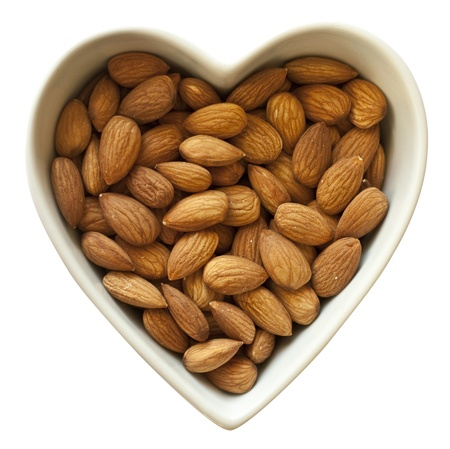 filled: Heart shaped bowl filled with healthy almonds Stock Photo